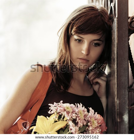 Sad young woman with a flowers at the wall - stock photo