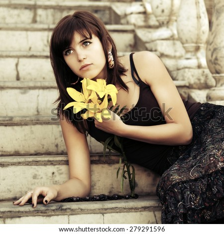 Sad young woman with a flowers sitting on steps - stock photo