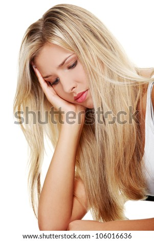 Sad, young woman with blond long hair is sitting and thinking looking down. - stock photo