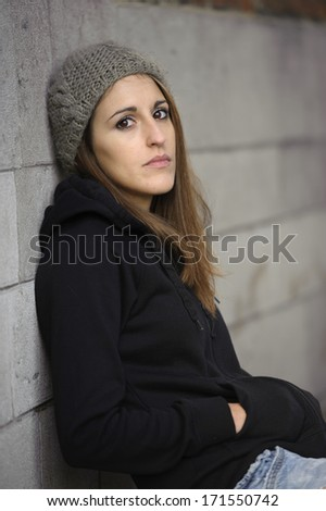 sad young woman with knitted hat , outdoors - stock photo