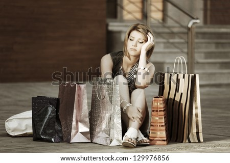 Sad young woman with shopping bags sitting on the sidewalk