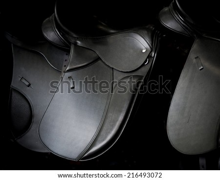 saddles on market stall - stock photo