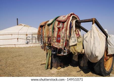 Saddles outside a nomadic herder's ger in the Gobi Desert, Mongolia - stock photo