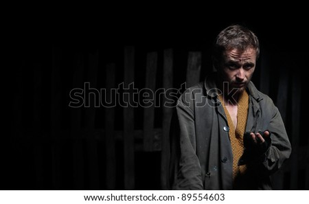 Sadly man in tramp's dirty wear looking to a camera. - stock photo