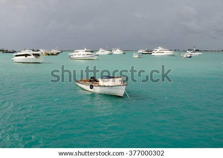 Safari boats anchored in a tranquil harbour with a turquoise blue water and rainy sky, Hulhumale, Maldives - stock photo