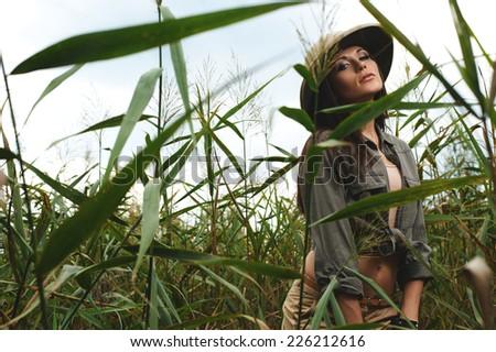 safari woman in swamp wearing safari hat in bulrush - stock photo
