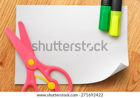 Safe scissors and markers on blank white piece of paper - stock photo