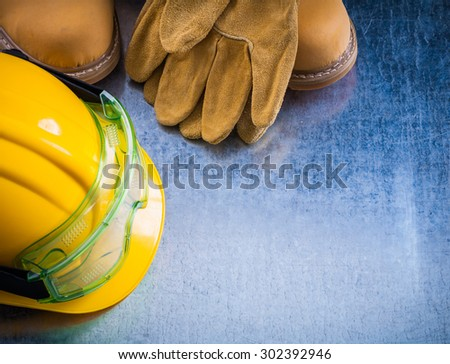 Safety boots protective working gloves hard hat and transparent plastic glasses on scratched metallic background construction concept. - stock photo