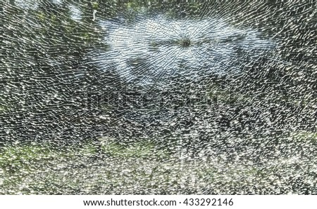 Safety broken window glass in day time, background of cracked window against green view - stock photo