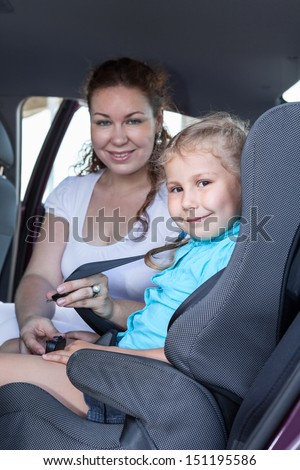 Safety children transportation with car seat in vehicle. Mother fastening daughter - stock photo
