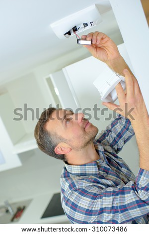 Safety conscious man fitting a fire smoke alarm - stock photo