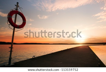 Safety equipment. Lifebuoy on the pier in the orange sunrise - stock photo