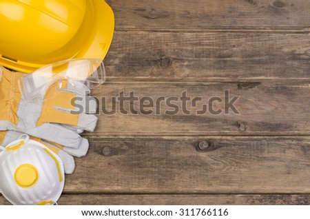 Safety equipment on wooden background with copy space - stock photo