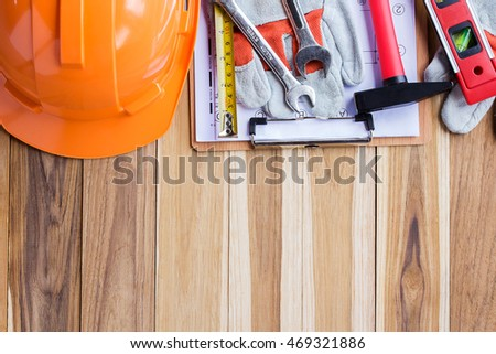 Safety equipment,tool kit and plan construction on wooden table background with copy space