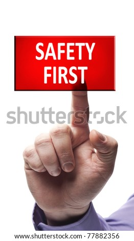 Safety first button pressed by male hand - stock photo