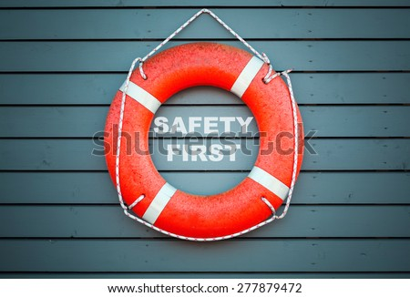 Safety first. Red lifebuoy hanging on blue wooden wall of a port building with the text label  - stock photo