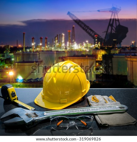 Safety gear kit and tools standing in front of oil refinery background  - stock photo