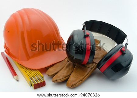 Safety helmet, hearing protection, ruler, pencil and work gloves - stock photo