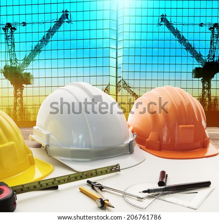 safety helmet on architect ,engineer working table with crane construction reflected on exterior modern building  - stock photo