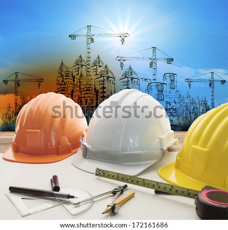 safety helmet on architect ,engineer working table with modern building and crane construction background use for construction business and civil engineering ,real estate topic - stock photo