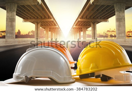 safety helmet on civil engineering working table against bridge construction in urban scene - stock photo