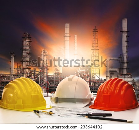 safety helmet on engineer working table against beautiful oil refinery in industry estate  - stock photo
