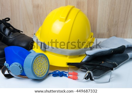 Safety helmet with other standard safety tools on white table and wood background.