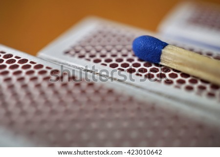Safety match stick with a small blue head on the top of box of safety matches with its black striking surface with the honeycomb shapes on the narrower side