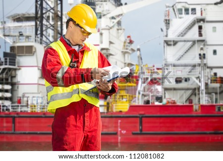 Safety officer, standing in front of a huge industrial platform, wearing overalls, a hard hat, safety goggles, and holding a clipboard with checklists - stock photo