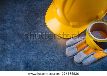 Safety tape hard hat and protective gloves on scratched metallic background copy space image construction concept. - stock photo