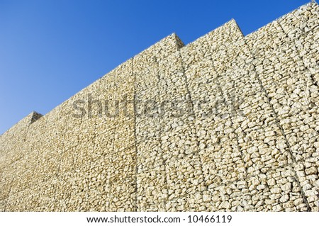Safety wall made of stacked meshed boxes of stones - stock photo