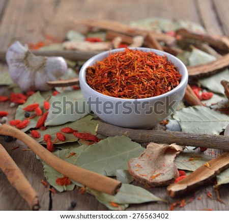 Safflower in the bowl on herbs background - stock photo