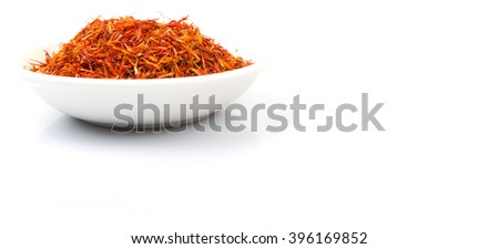 Safflower in white bowl over white background - stock photo