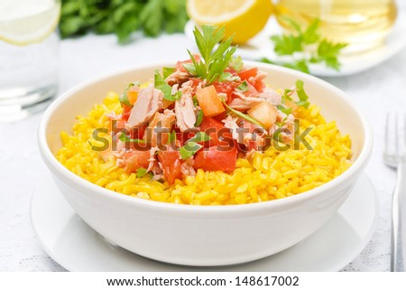 saffron rice with tuna, tomatoes, peppers and herbs in a bowl, close-up, horizontal