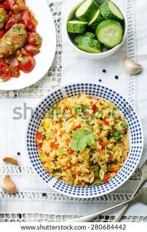 saffron rice with vegetables and cilantro on a white background. the toning. selective focus