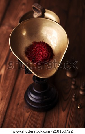 saffron spice in antique vintage iron scale bowl  on wooden table, shallow dof - stock photo