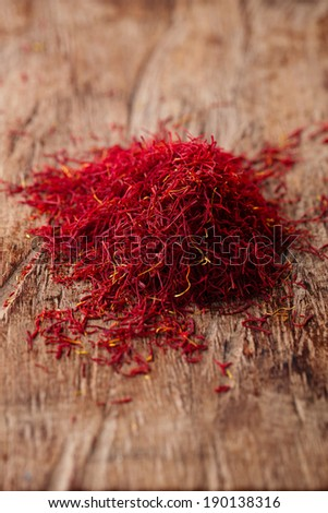 saffron spice in pile on old wooden background, closeup - stock photo