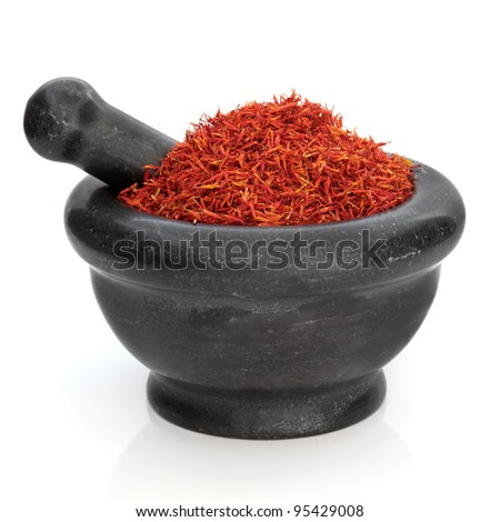 Saffron used in traditional chinese herbal medicine in a black granite mortar with pestle isolated over white background. Hong Hua.  Flos carthami tinctori. - stock photo