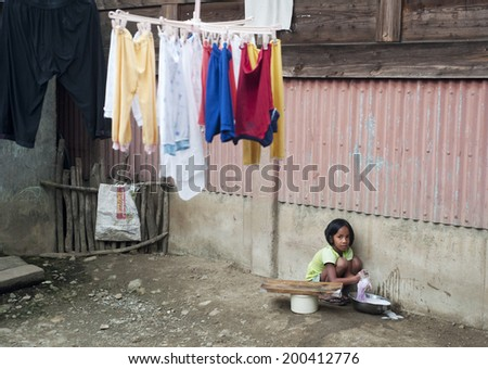 SAGADA, PHILIPPINES - MARCH 23, 2012: Girl washing clothes in the small village in Philippines. About 12 per cent of Philippines children between the ages of five and 14 are forced to work.  - stock photo
