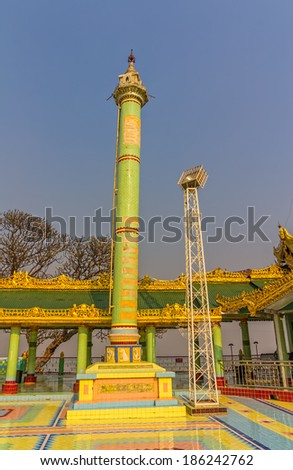 SAGAING HILL, MYANMAR - FEBRUARY 26, 2013: Votive green column in buddhistic temple at the top of Sagaing hill near Mandalay.