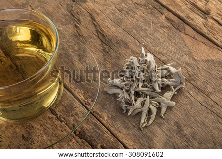 sage tea and sage leafs on wooden table - stock photo