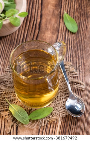 Sage Tea in a small glass on wooden background - stock photo