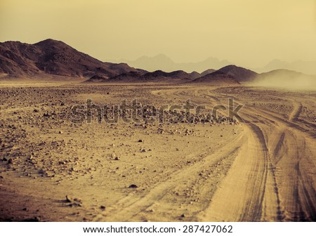 Sahara desert at sunset - mountain landscape with dust off road and stone hills on a horizon. Exotic adventure and expedition in arid wilderness. Safari and extreme travel in Africa. - stock photo