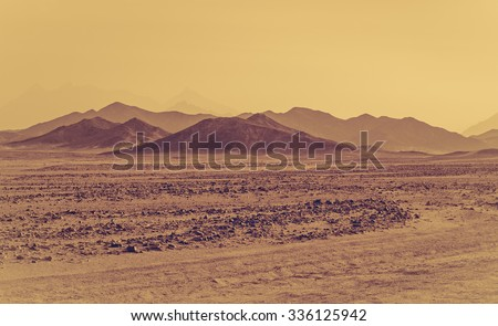 Sahara desert - mountain landscape and stone hills silhouettes on a horizon. Exotic adventure in Arabian desert, extreme travel to Egypt. Sandstorm in african desert. Extreme safari on off-road car. - stock photo