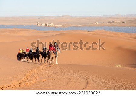 SAHARA, MOROCCO - 26 NOV: Camel caravan with tourists in the sahara desert.  November 26, 2008 in Morocco, Africa