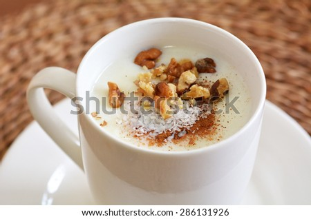 Sahlab Salep drink with shredded coconuts, crushed nuts and  pinch of cinnamon.Food and drinks background texture. - stock photo