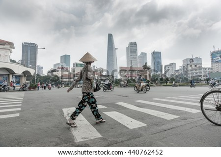 SAIGON, VIETNAM - OCTOBER 12; overcast desaturated colors at major intersection woman on pedestrian crossing wearing coolie hat motorbikes, cycles randomly move October 12, 2013 in Saigon, Vietnam.