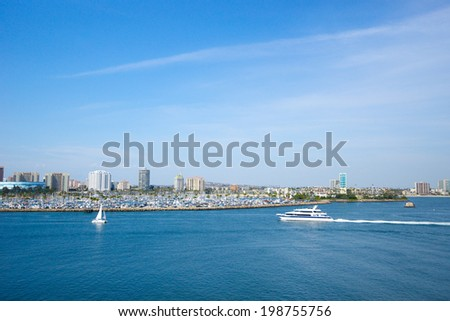 Sail boat and large yacht cruise across Long Beach's harbor in southern California.