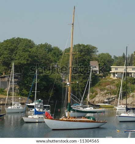 Sail boat in the harbor anchored at Perkins Cove pier in Ogunquit Maine . - stock photo