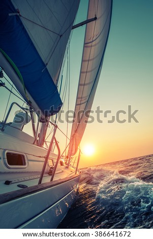 Sail boat moving in the open sea at sunset